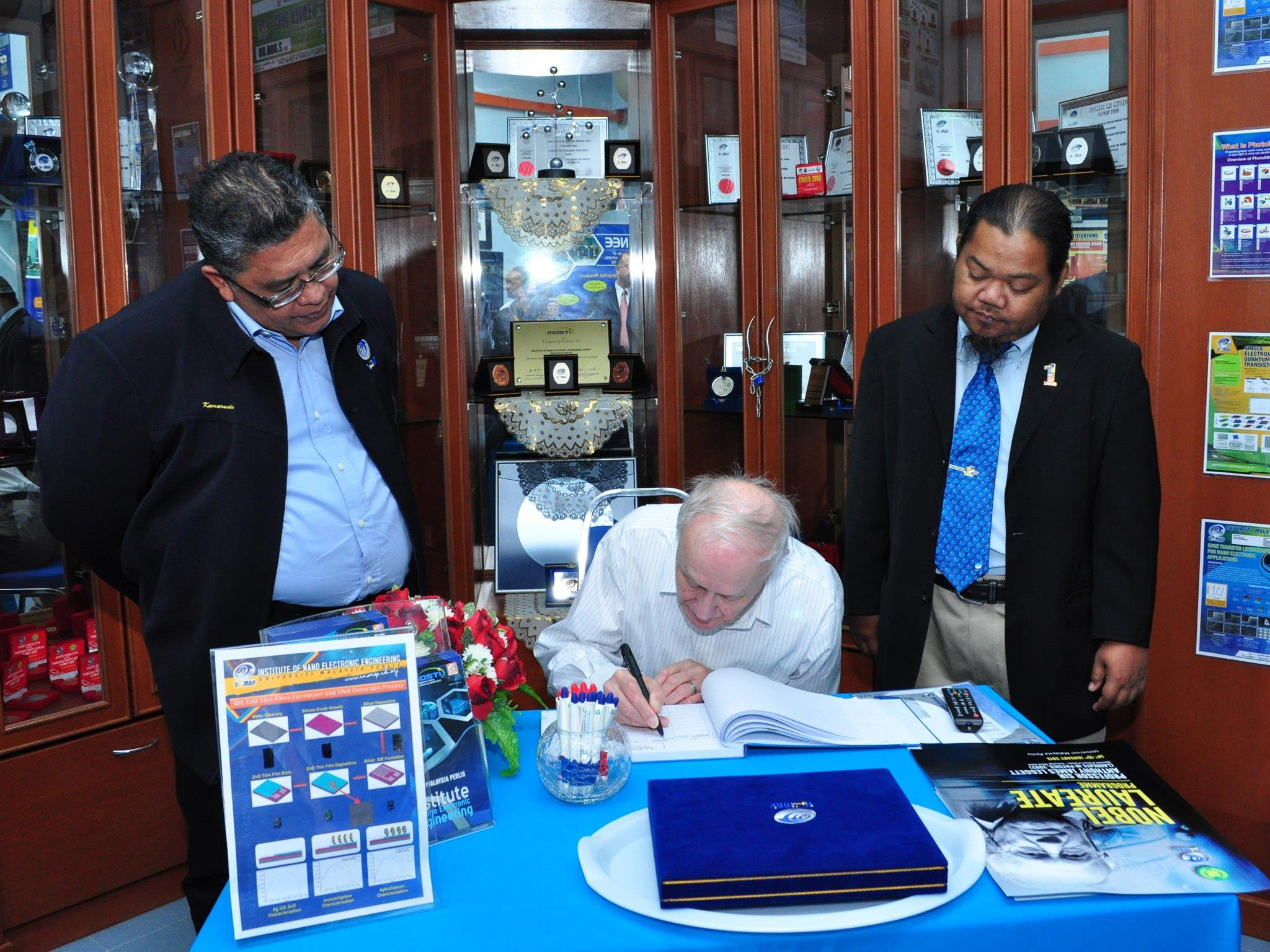 Prof. Sir Anthony J. Leggett signing the INEE guestbook.